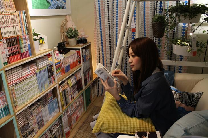 「マンガ好きの部屋」で、持参したマンガを読む外川礼子。