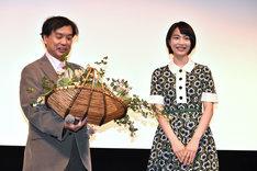 のん(右)から花を受け取る片渕須直監督。