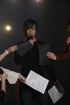 色黒であることをイジられた浪川大輔は、舞台裏を全身黒の衣装で歩いていた際に「鳥海(浩輔)さんに『服着ろよ』って言われた」と明かす。写真はそんな浪川に「隠してください」と台本を被せるキャスト陣の様子。