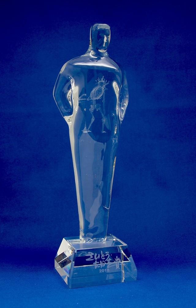 正賞として贈られたゴルゴ13を模したクリスタル像。さいとう・たかをがデザインを監修しており、作品を象徴する茨のかんむりを被ったガイコツが胸部に浮かび上がる特殊仕様。