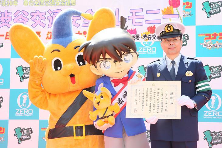 渋谷警察署長(右)とピーポくん(左)と記念撮影をするコナン(中央)。