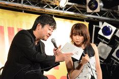 「未来のミライ」サウンドトラックの歌詞カードを上白石萌歌に見せる細田守監督。