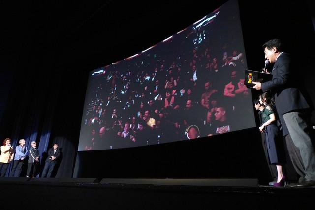 アメリカで行われた試写会の様子が映し出されたスクリーン。