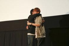 「『DOUBLE DECKER! ダグ&キリル』トークショー付きEXTRA一挙上映会」の様子。降壇間際、抱擁する三上哲(左)、天崎滉平(右)。