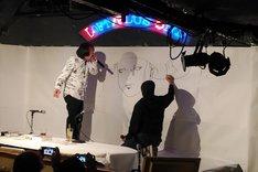 紙製マッキーの使い心地を、ペン先の絵を描いて説明する寺田。祖父江は「あっ、そこに描く……?」と苦笑い。