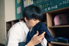 映画「惡の華」より、伊藤健太郎扮する春日高男が体操着を嗅ぐ姿を捉えた場面写真。
