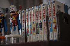 川口たろう作「超ヒーロー伝説 バックマン」も部屋の片隅に並んでいる。(c)2015映画「バクマン。」製作委員会