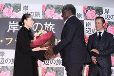 花束を受け取る深津絵里(左)とそれを笑顔で見守る浅野忠信(右)。
