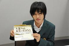 土屋太鳳へのメッセージを書いたプレートを手にした山崎賢人。