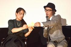 安藤玉恵(左)に、自身がイラストを手がけたステッカーを見せるリリー・フランキー(右)。