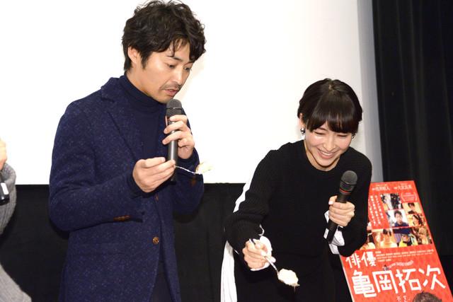 安田顕の顔がデザインされたケーキの、目の部分を笑顔でくり抜く麻生久美子(右)。