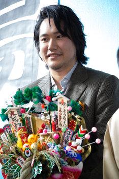 三遊亭小遊三から贈られた熊手を持つ松山ケンイチ。