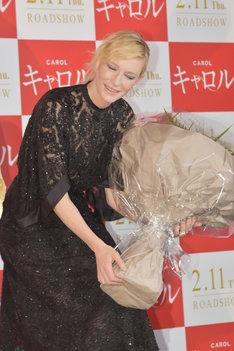 「花束が重くて抱えきれない!」と言わんばかりのポーズを取ってみせるケイト・ブランシェット。
