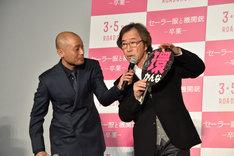 観客に借りたうちわで「環」の漢字の意味を解説する武田鉄矢(右)と、サポートする宇野祥平(左)。