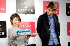 ロマンスカー型チョコレートケーキを手にする大島優子(左)と、鮮やかなブルーに微妙な表情を浮かべる大倉孝二(右)。
