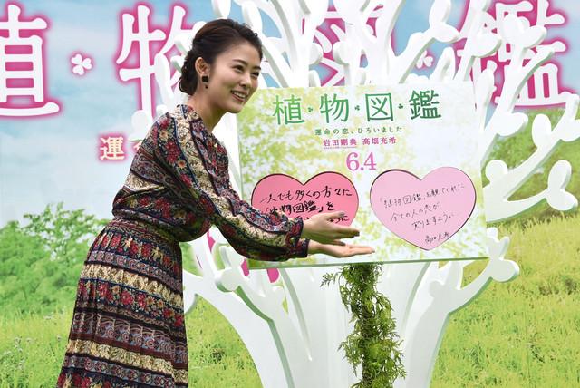 「恋愛成就の木」にメッセージをはめ込む高畑充希。