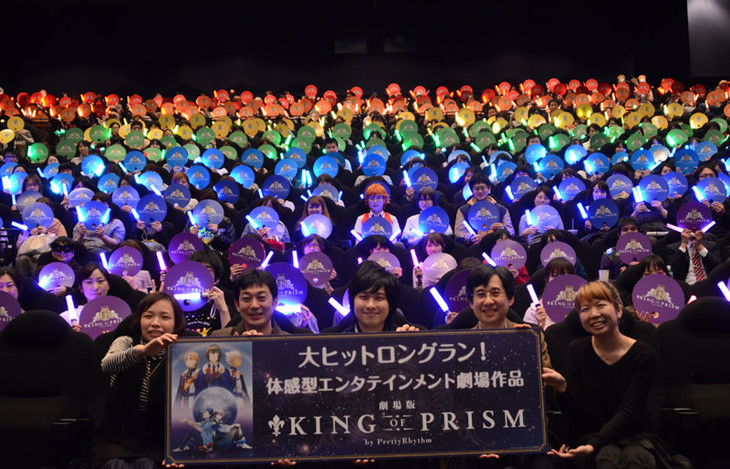 「KING OF PRISM 公開3カ月突入! サンキュー▽上映会」の様子。観客が列ごとに色の異なるうちわを掲げて、虹がかかったような光景が作り出された。