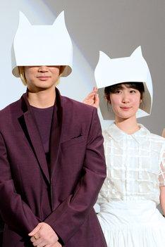 """劇中に登場する""""猫かんむり""""を被る綾野剛(左)と黒木華(右)。"""