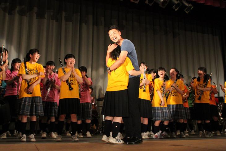 北海道・札幌白石高校の吹奏楽部員にハグする竹内涼真(右)。