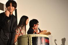岡田将生に、樽の中のメープルシロップを舐めるよう指示する松坂桃李(左)。