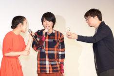新海誠(右)の携帯でセリフを確認し、劇中シーンを実演する神木隆之介(中央)と上白石萌音(左)。