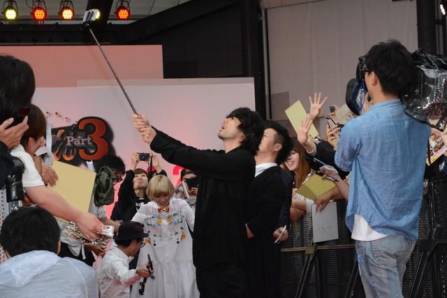 自撮り棒を使いファンとの写真撮影を行う山田孝之。