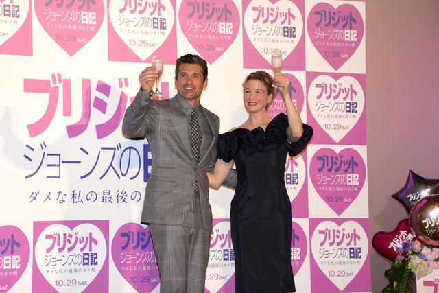 「カンパイ!」の音頭とともにグラスを掲げるレニー・ゼルウィガー(右)とパトリック・デンプシー(左)。