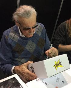 フィギュアの箱にサインをするスタン・リー。