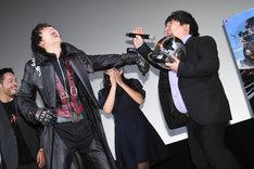 腕に装着したカメラで、井口昇(右)を撮影する中村優一(左)。