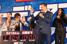 ボタンを押そうとする山寺宏一(左)とクリス・プラット(右)。