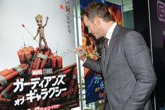 「ガーディアンズ・オブ・ギャラクシー:リミックス」のポスターにサインをするクリス・プラット。