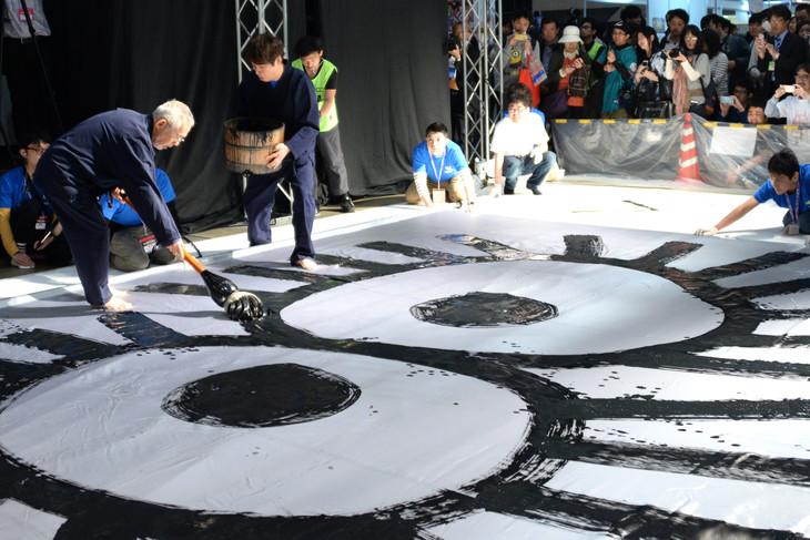 「ニコニコ超会議2017」で大書パフォーマンスを行う鈴木敏夫(左奥)。