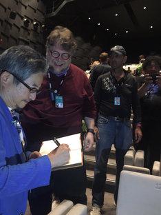 ギレルモ・デル・トロ(左から2番目)の持参したノートにマジンガーZのイラストを描きサインを添える永井豪(左端)。