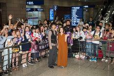 空港でファンと記念撮影をする上戸彩(右)と斎藤工(左)。