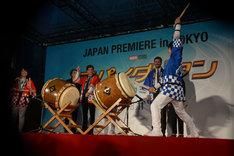 和太鼓の演奏を見ながら腕を上下に動かすトム・ホランド(中央奥)。