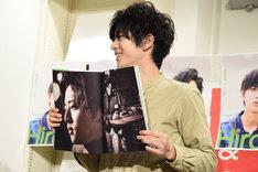 お気に入りのページを広げる飯島寛騎。