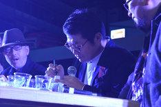 ファンが持参したペットボトルにサインをする松尾諭。