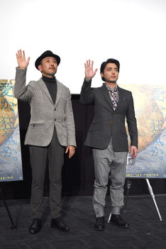 ムービーカメラに向かってゆっくりと手を振る山田孝之(右)とFROGMAN(左)。