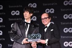 「GQ JAPAN」の鈴木正文編集長からトロフィーを受け取った野田洋次郎(左 / RADWIMPS、illion)。