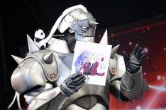賞品の荒川弘のサイン入り色紙を手にする、グランプリを獲得したコスプレイヤー。