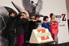 巨大なケーキを囲んでポーズを決める登壇者たち。