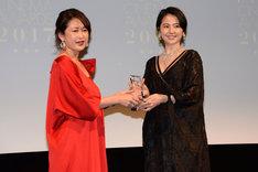 長澤まさみ(右)がELLE編集長の坂井佳奈子(左)からトロフィーを受け取る様子。