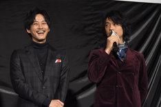 松坂桃李(左)と、パディントンにぬるぬるプロレスのバイトを薦める斎藤工(右)。