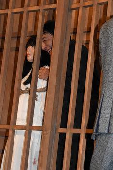 檻の中でサニー人形とポーズを取るピエール瀧。
