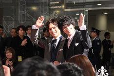 夫婦のように腕を組んでレッドカーペットを歩く岡田龍太郎(左)と飯島寛騎(右)。