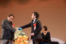 ムロツヨシ(右)に渋々花束を渡す福田雄一(左)。