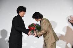染谷将太に花束を手渡す野田洋次郎(Vo, G, Piano / RADWIMPS)。