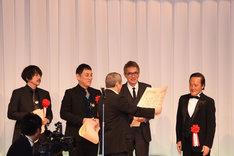 1人だけ仰々しく表彰状を読み上げられ、照れる金田時男(右)。
