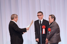 ビートたけし(左)から表彰状を授与される西田敏行(右手前)と塩見三省(右奥)。