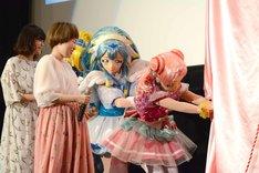 パネルを運ぶキュアエール、キュアアンジュ、キュアエトワールを見守る本泉莉奈(左)と引坂理絵(左から2番目)。